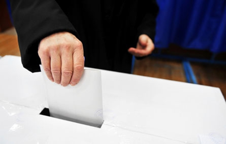 Photo of man dropping vote into box